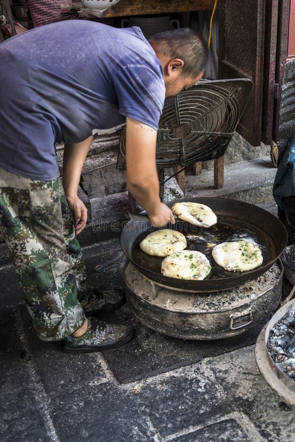 Uomo che cucina pane piano tradizionale con le verdure e la carne, Cina immagini stock libere da diritti