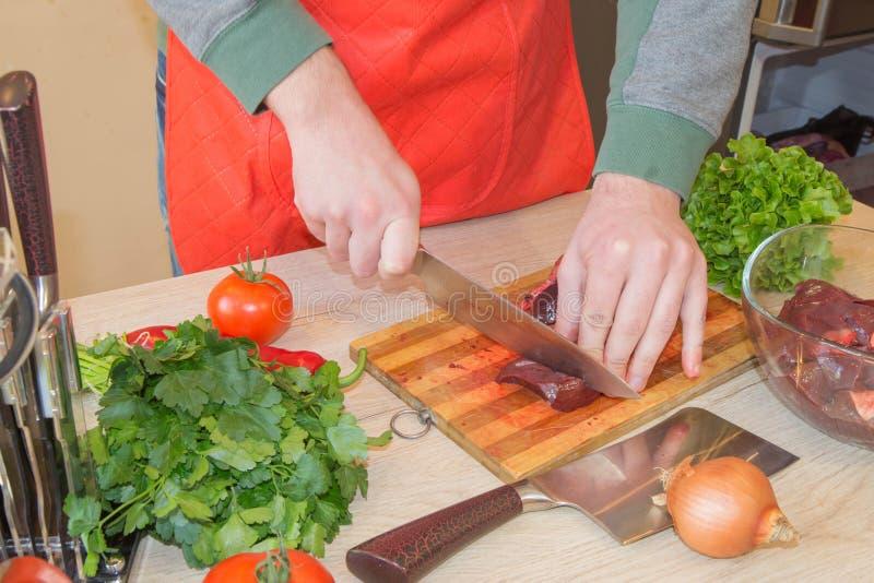 Uomo che cucina pasto nella cucina Giovane carne maschio di taglio del cuoco unico sul bordo di legno immagine stock libera da diritti