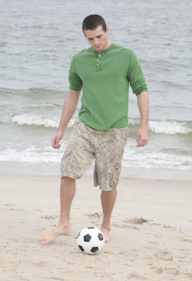 Uomo che dà dei calci alla sfera di calcio fotografia stock