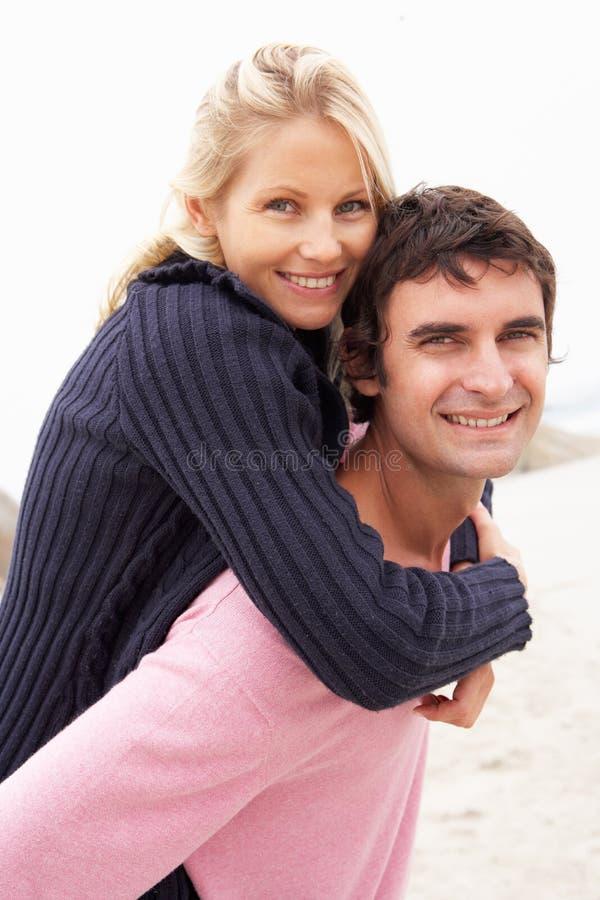 Uomo che dà a due vie della donna sulla spiaggia di inverno immagine stock