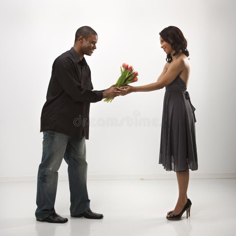 Uomo che dà i fiori della donna. fotografia stock