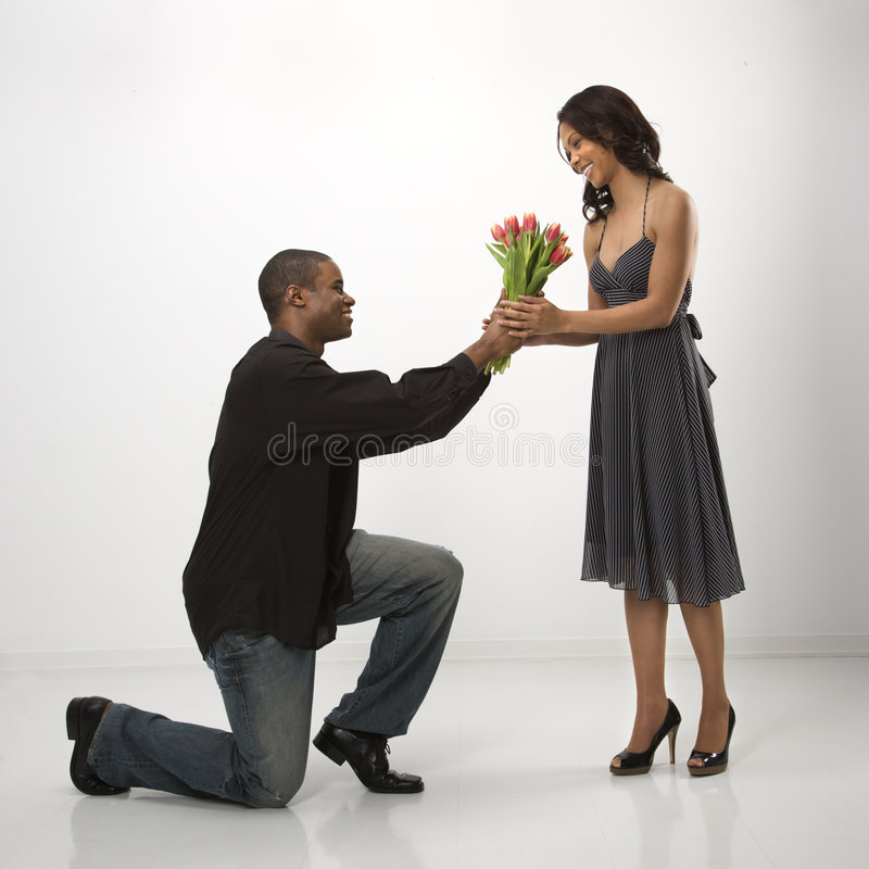 Uomo che dà i fiori della donna. immagini stock
