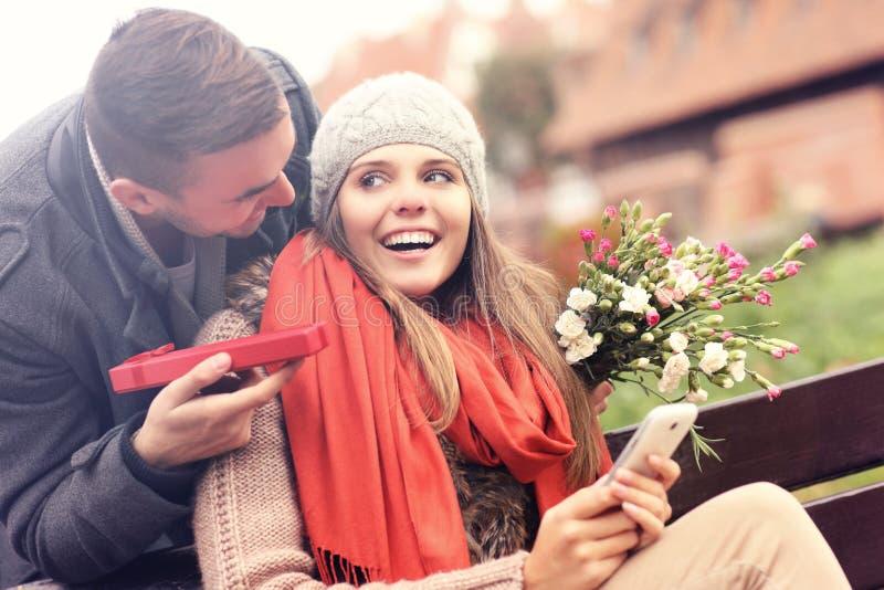 Uomo che dà il regalo di sorpresa alla donna nel parco fotografia stock