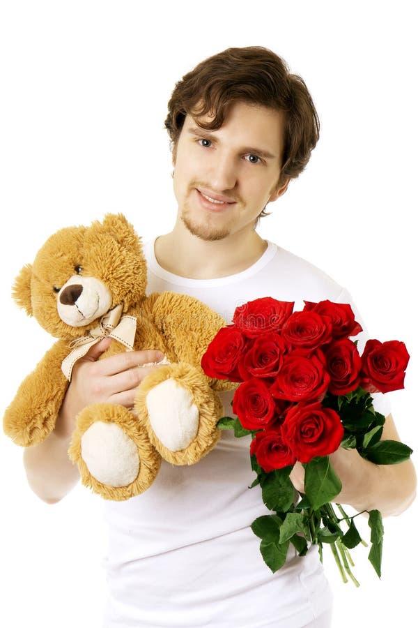 Uomo che dà l'orso e un mazzo delle rose immagini stock libere da diritti