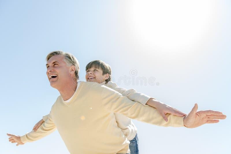 Uomo che dà sulle spalle giro al figlio contro il chiaro cielo blu fotografie stock