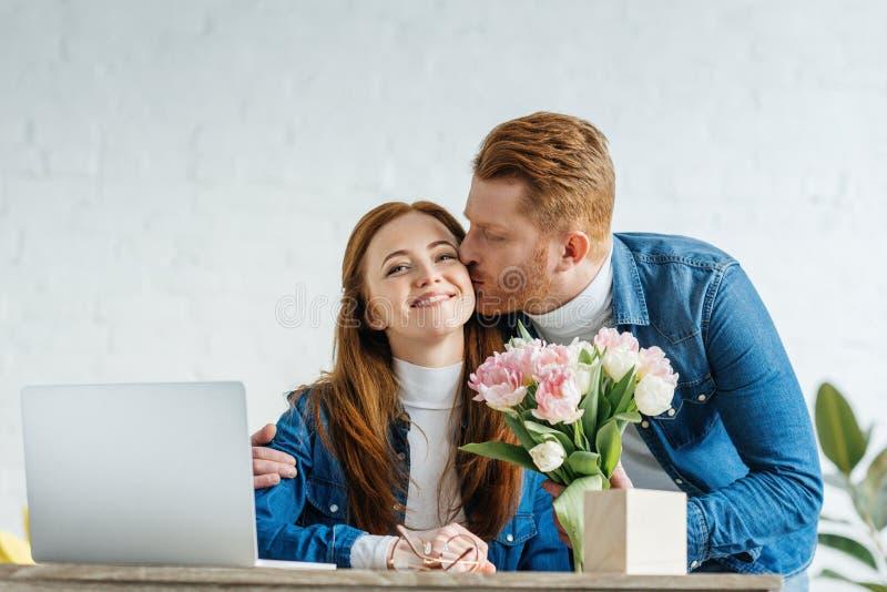 Uomo che dà un mazzo dei tulipani alla giovane donna immagine stock