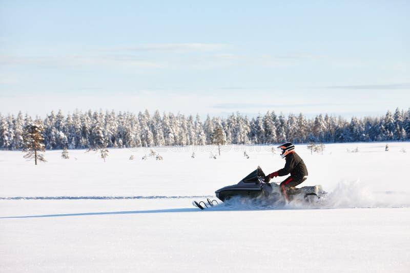 Uomo che determina gatto delle nevi in Finlandia immagini stock