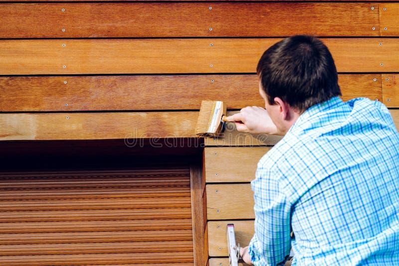 Uomo che dipinge parete di legno con una spazzola fotografie stock