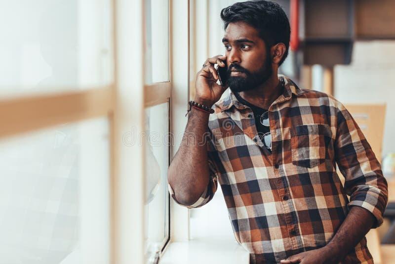 Uomo che discute a fondo condizione del telefono cellulare accanto ad una finestra fotografia stock