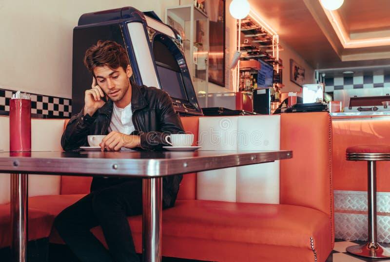 Uomo che discute a fondo telefono cellulare che si siede ad un ristorante fotografia stock