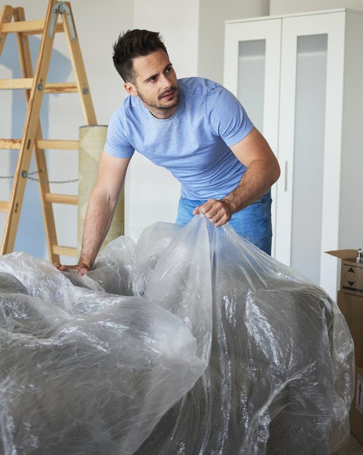 Uomo che disimballa la sua roba durante la casa commovente fotografia stock libera da diritti