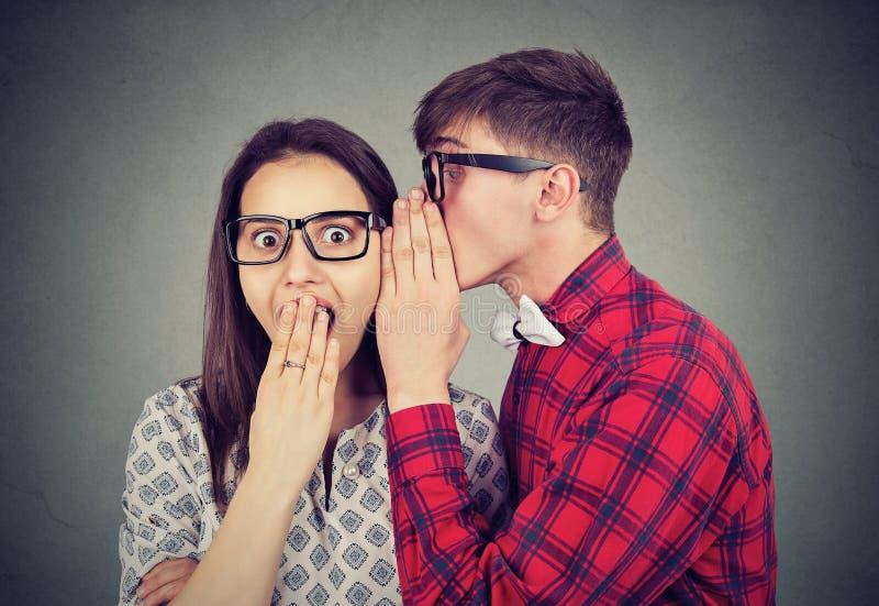 Uomo che divide i pettegolezzi con la donna fotografie stock