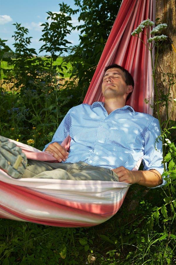 Uomo che dorme in hammock fotografia stock