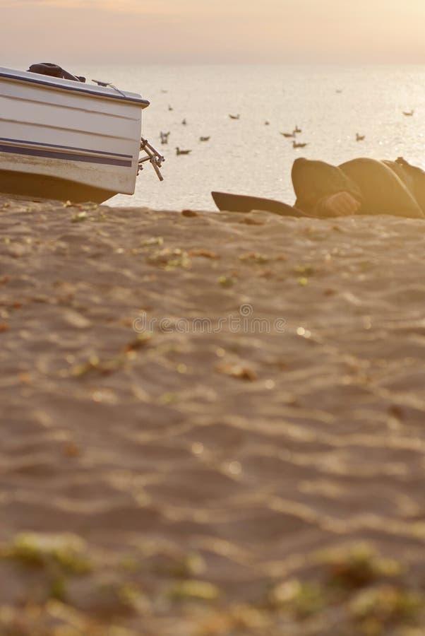 Uomo che dorme sulla spiaggia fotografia stock libera da diritti