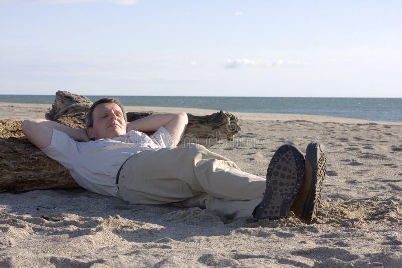 Uomo che dorme sulla spiaggia fotografie stock