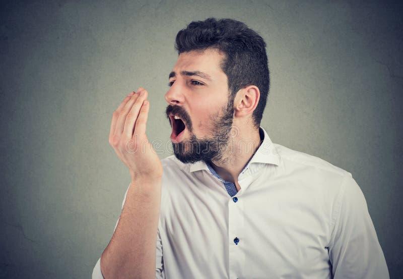 Uomo che effettua una prova del respiro della mano fotografia stock