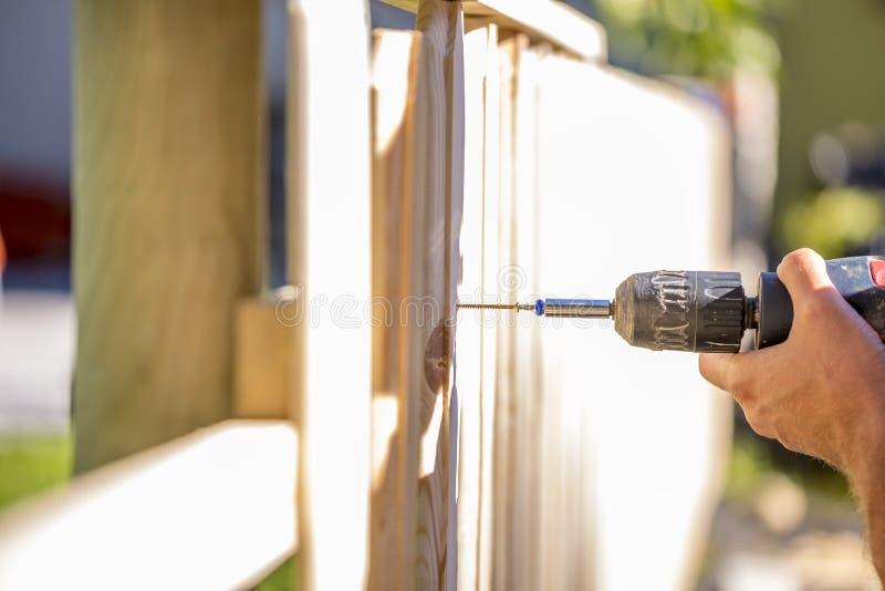 Uomo che erige un recinto di legno all'aperto fotografia stock