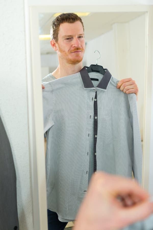 Uomo che esamina camicia a casa fotografia stock