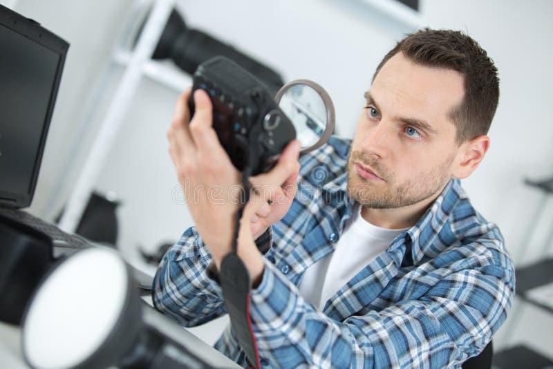Uomo che esamina corpo della fotocamera con la lente d'ingrandimento immagine stock libera da diritti