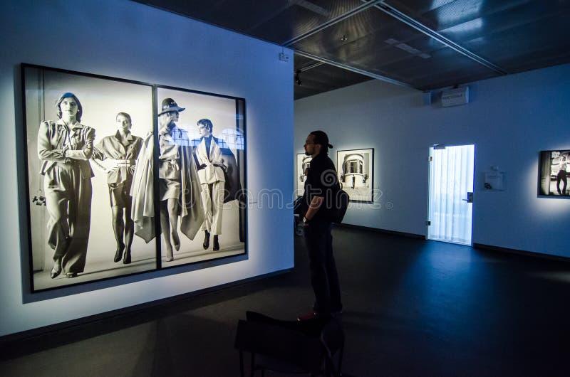 """Uomo che esamina il lavoro """"Sie Kommen"""" di Helmut Newton immagini stock"""