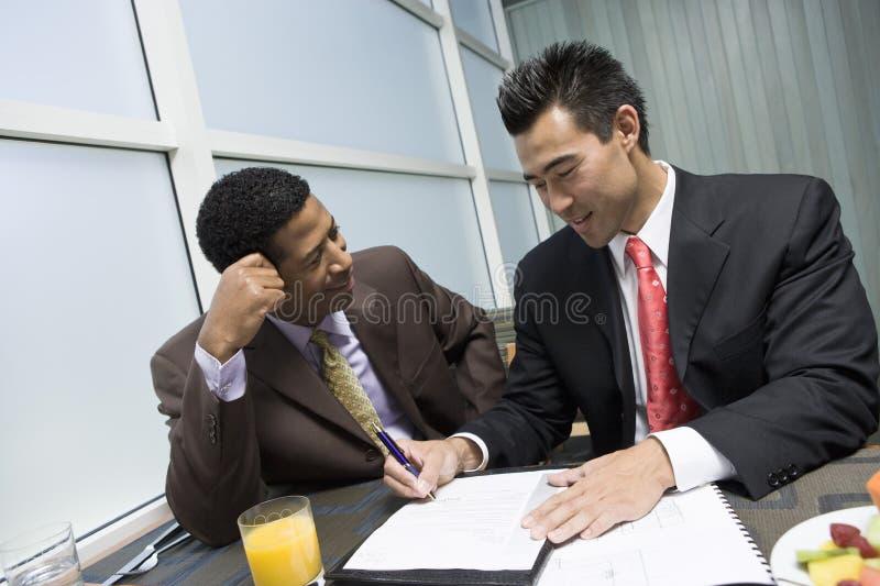 Uomo che esamina il suo documento di firma del socio commerciale fotografia stock libera da diritti