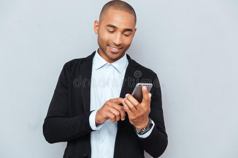 Uomo che esamina il suo Smart Phone mentre invio di messaggi di testo fotografia stock libera da diritti