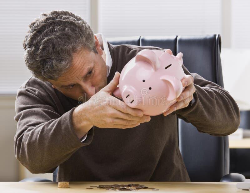 Uomo che esamina la Banca Piggy immagini stock libere da diritti
