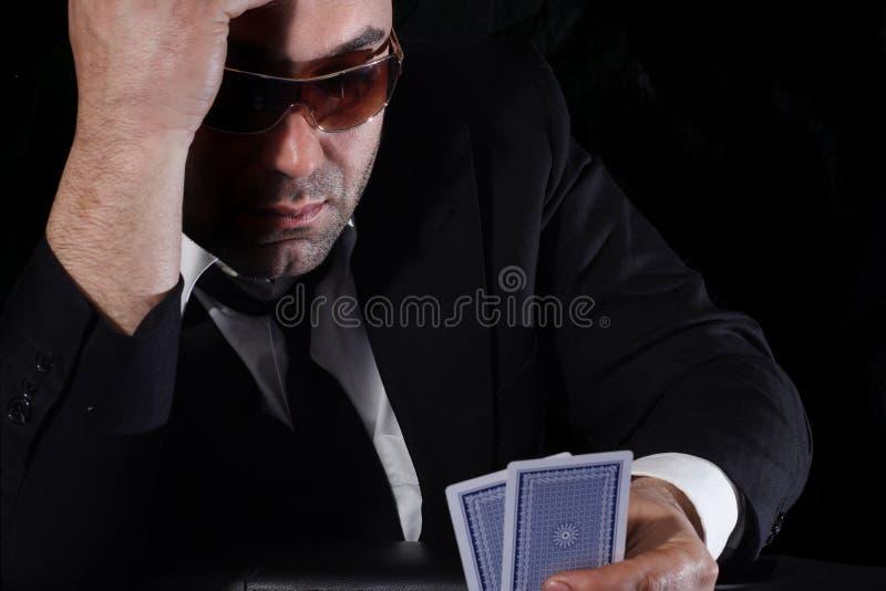 Uomo che esamina le schede in casinò immagine stock libera da diritti