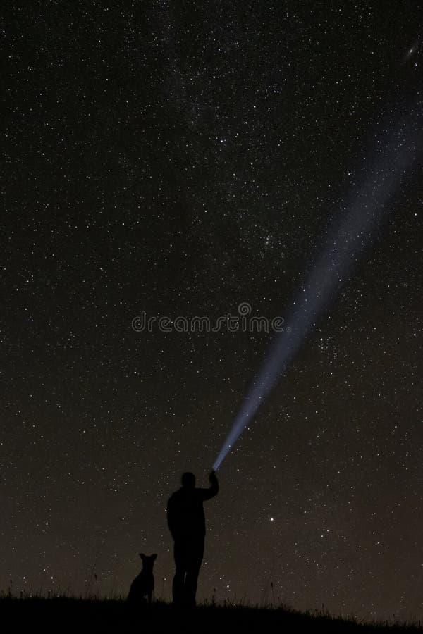 Uomo che esamina le stelle con il suo cane fotografia stock libera da diritti