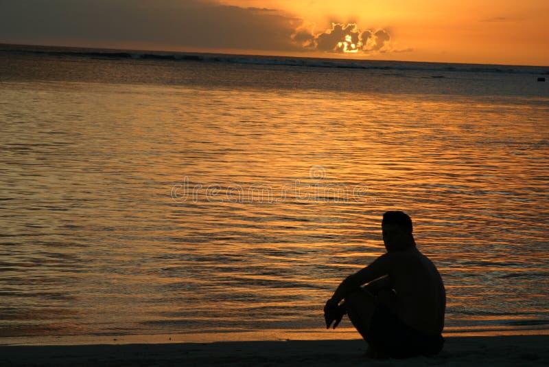 Uomo che esamina tramonto sopra l'Isola Maurizio fotografia stock libera da diritti