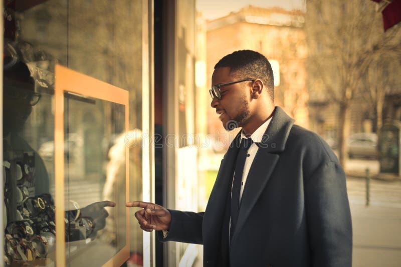 Uomo che esamina una vetrina fotografie stock