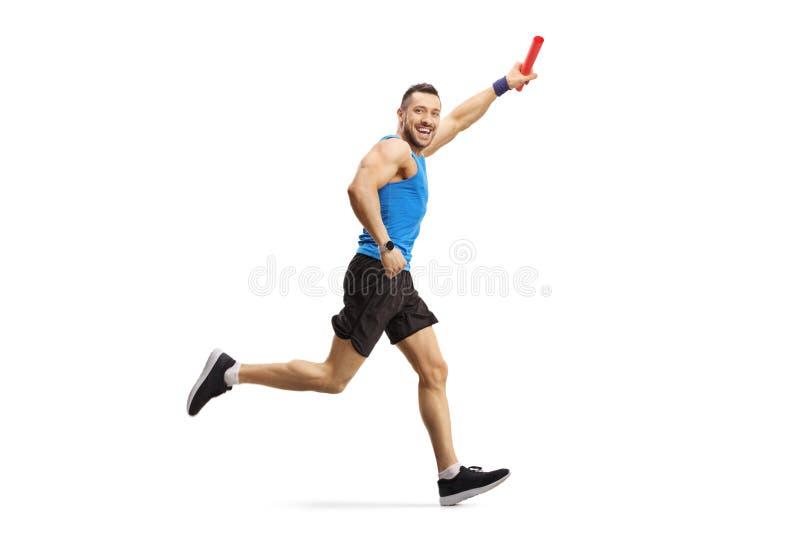 Uomo che esegue una corsa di relè con un bastone in sua mano fotografia stock libera da diritti