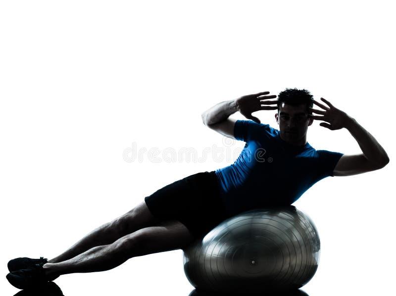 Uomo che esercita posizione della sfera di forma fisica di allenamento fotografie stock libere da diritti