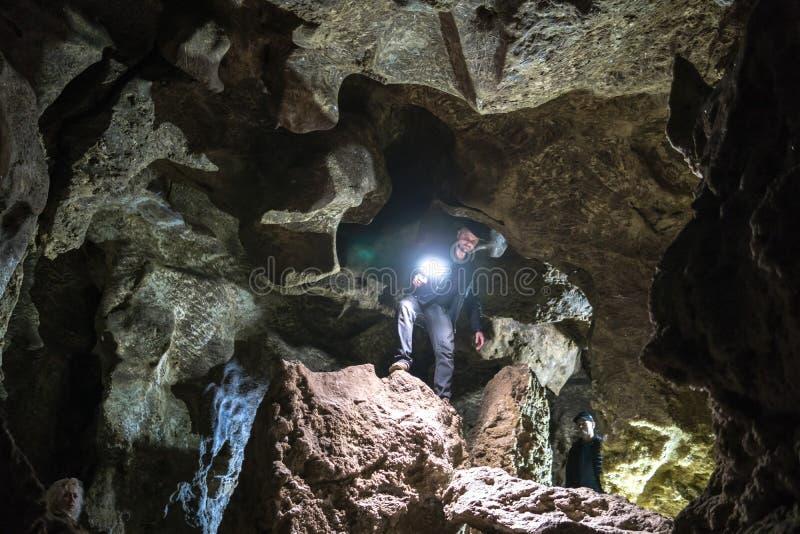 Uomo che esplora caverna enorme I viaggiatori di avventura hanno vestito il cappello da cowboy ed il bomber vacanza estrema, itin immagini stock libere da diritti