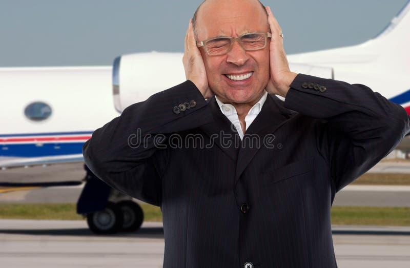 Uomo che esprime sforzo e rumore all'aeroporto immagine stock libera da diritti