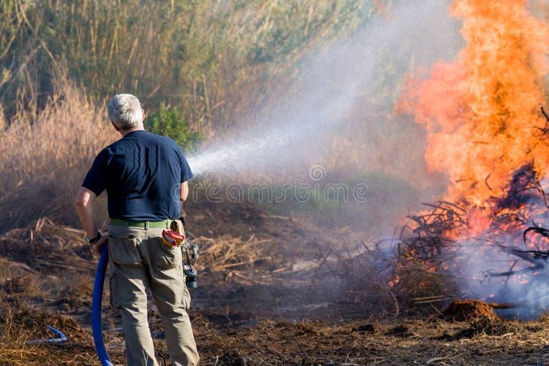 Uomo che estingue fuoco fotografia stock libera da diritti