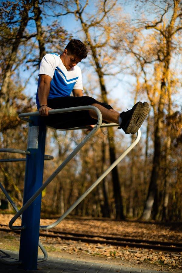 Uomo che fa allenamento dell'ABS sulle parallele simmetriche all'aperto sulla caduta durante il tramonto immagini stock libere da diritti