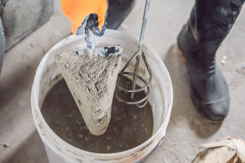 Uomo che fa cemento con un miscelatore della costruzione in un secchio fotografia stock libera da diritti