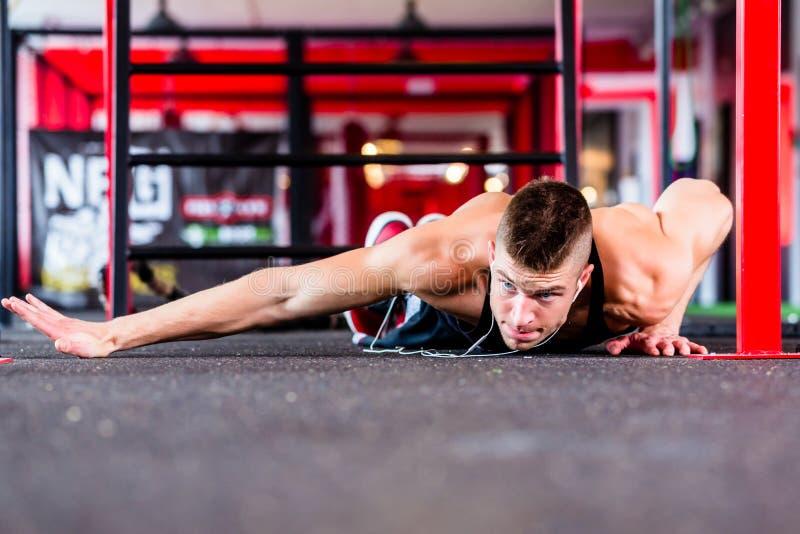 Uomo che fa flessione nella palestra di forma fisica di sport fotografie stock