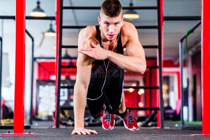 Uomo che fa flessione nella palestra di forma fisica di sport immagini stock