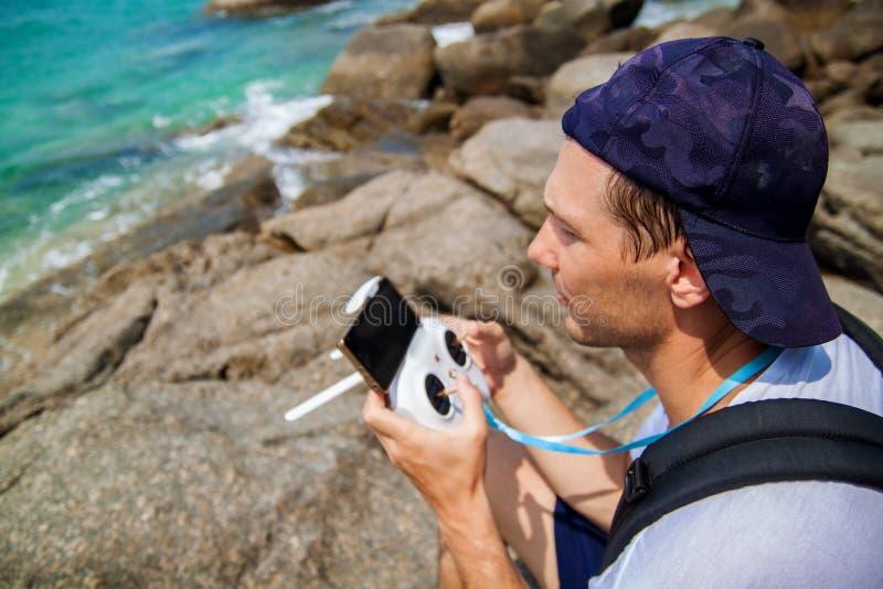 Uomo che fa funzionare un fuco con telecomando sulla spiaggia immagine stock libera da diritti