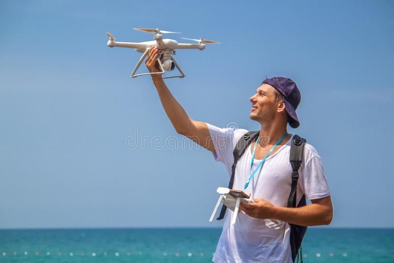 Uomo che fa funzionare un fuco con telecomando sulla spiaggia fotografia stock libera da diritti