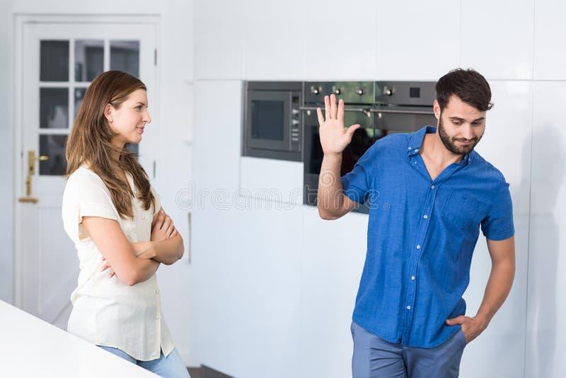 Uomo che fa gesto di arresto alla moglie mentre discutendo fotografie stock libere da diritti