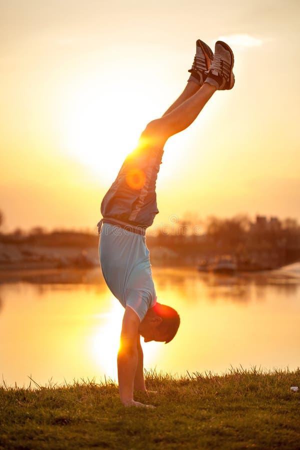 Uomo che fa i verticali sul tramonto fotografia stock libera da diritti