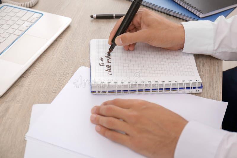 Uomo che fa la lista di da fare mentre sedendosi alla tavola, primo piano fotografia stock