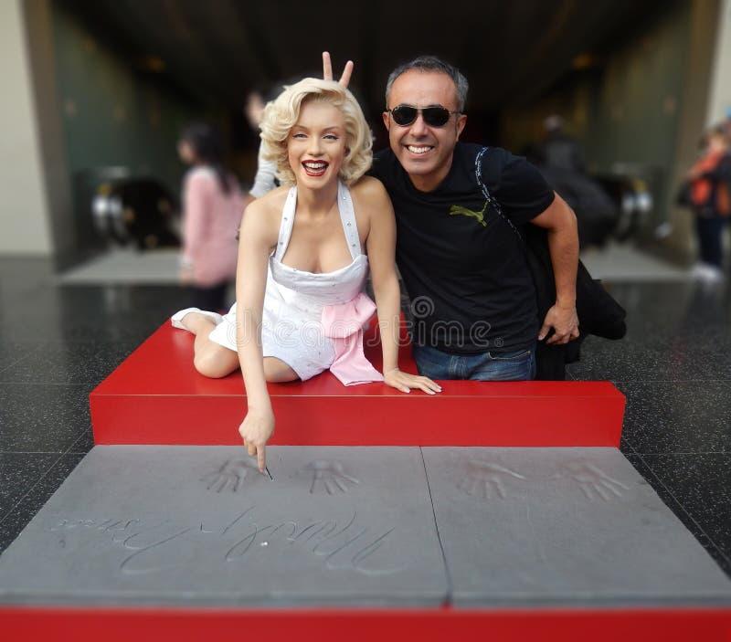 Uomo che fa le orecchie del coniglietto dietro il ` s di Marilyn Monroe dirigersi al Mada fotografia stock libera da diritti