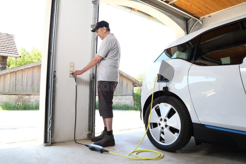Uomo che fa pagare automobile elettrica allo sbocco a casa fotografia stock libera da diritti