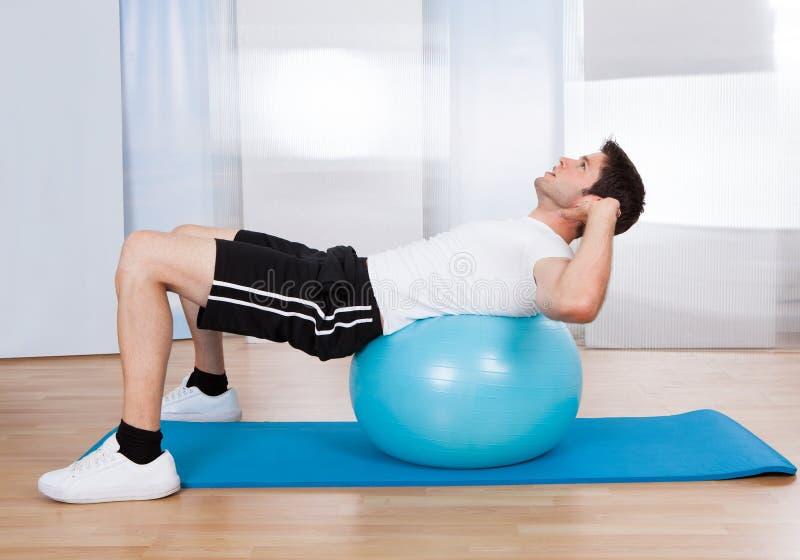 Uomo che fa Sit Ups On Fitness Ball fotografia stock