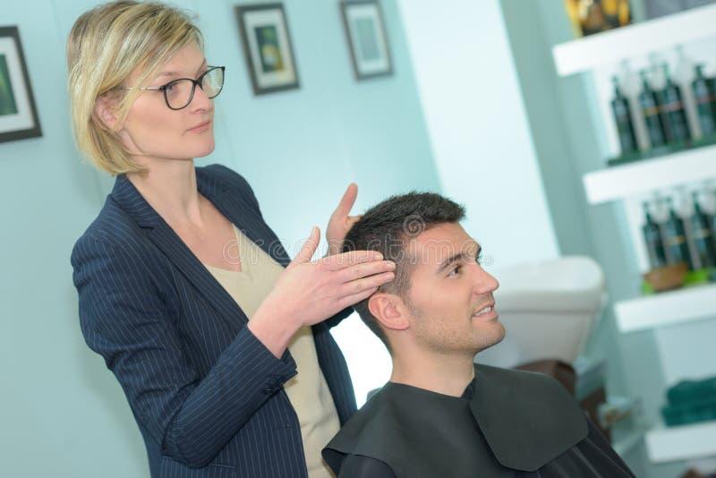 Uomo che fa tagliare capelli nel salone di lavoro di parrucchiere fotografia stock