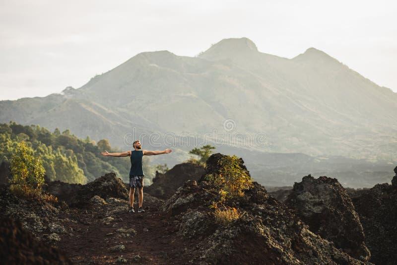 Uomo che fa un'escursione e che gode del Mountain View vulcanico immagine stock